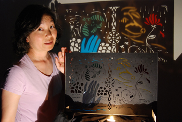 Photo of Leslie K. Gray and a whimsical shadow art piece she created